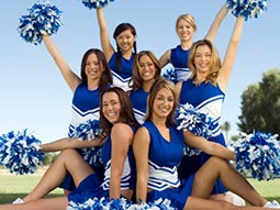 Close up of women in blue and white cheerleader costumes, posing outdoors and holding up pom poms