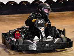 A man riding a black kart on an indoor karting track