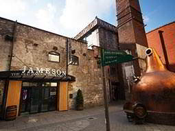 The exterior of the Jameson distillery with a large copper still outside