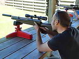 A man aiming a rifle down a range