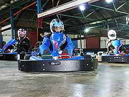 Three go karts racing on an indoor circuit