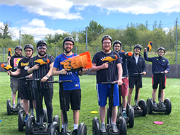 Five people holding polo mallets while standing on segways in a field