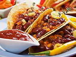 A plate with three tacos and a bowl of sauce on - more food visible in the background
