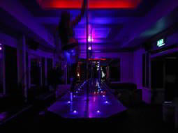 A runway and pole at a strip club with a woman standing on
