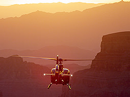 A flying helicopter with a bright sun behind it