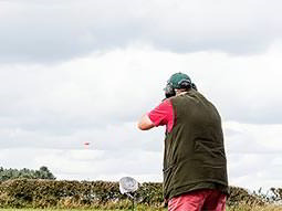 A man aiming a shotgun into the sky, with an orange clay visible