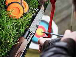 A split image of a shotgun lying on grass near orange clays and a person aiming a bow and arrow