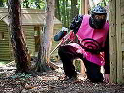 A man wearing a paintball mask and a pink bib with a target on crouching next to a wooden fence and holding a paintball gun