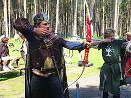 A man dressed as a knight, preparing to fire an arrow from a bow with others dressed up in the background