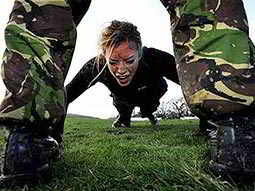 A woman doing a press-up on grass, viewed between a pair of legs wearing camouflage trousers