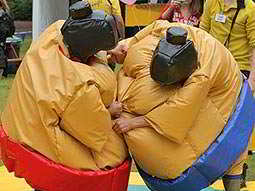 Two people wrestling in large 'sumo' suits and hats