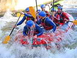 A group of people paddling a red raft through turbulent rapids