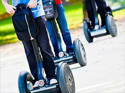 A person riding a segway with just their legs and wheels visible