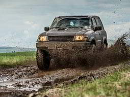 A 4x4 vehicle driving down a muddy track in a forest