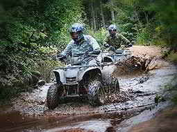 Two quad bikes being driven through a large, muddy puddle