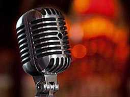 A close up of a silver microphone to a backdrop of lights