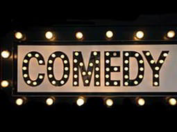 The word comedy illuminated in lights
