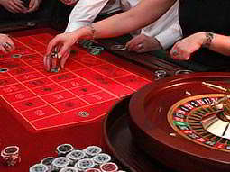 A roulette wheel and table, surrounded by people