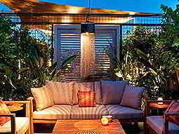 An outside seating area with shades and plants