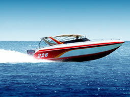 A speedboat on the water with blue sky in the background