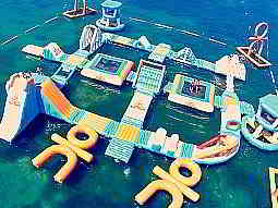 A large inflatable obstacle course with trampolines floating in the sea