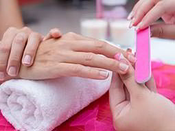 A hand resting on a rolled-up towel, receiving a manicure