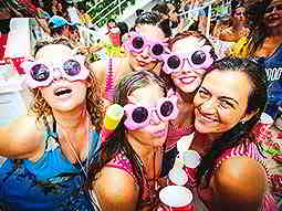 A group of ladies, some wearing matching pink sunglasses, pose in a large crowd of people