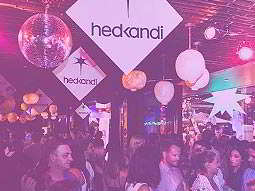 A group of people standing under purple lights and hedkandi signs