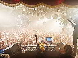 Multiple people dancing in a DJ booth overlooking a large, filled dancefloor