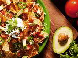 A plate of nachos on a wooden board, next to half an avocado