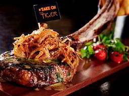 Steak topped with onions alongisde salad and served up on a wooden board