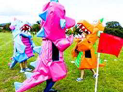 Three people dressed in purple, blue and orange dragon costumes in a field
