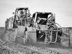 Black and white image of a line of rage buggies, driving through a muddy field