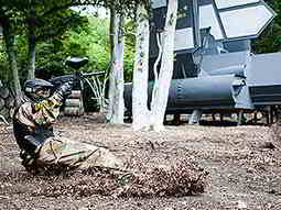 A person wearing camouflage overalls and a mask skidding across the ground and aiming a paintball gun