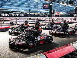 Four black go karts lined up for a race on an indoor karting track