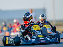 A man driving an outdoor kart, with a person racing in the background