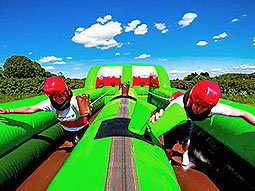 Two people running on a green bouncy castle with red helmets on, in a field