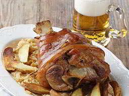 A glass of beer and a chicken meal on a wooden table