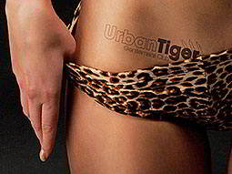 A close up of a woman in leopard print knickers, pulling them down slightly to reveal Urban Tiger ink