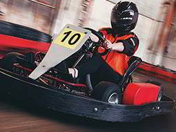 A person racing a go kart on an indoor track in a helmet and red overalls