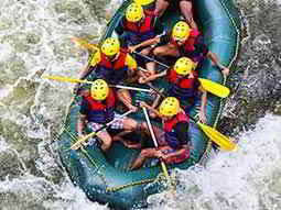 Seven people in a rubber dinghy, battling white water rapids