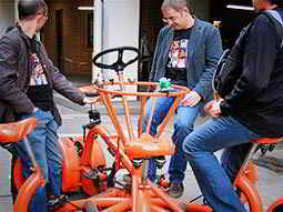 Three men sat on a conference bike