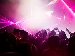 People dancing in a club to a backdrop of pink light