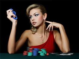 A woman in a red dress holding blue casino chips with more piled in front of her