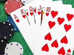 Five red hearts cards laid out next to poker chips