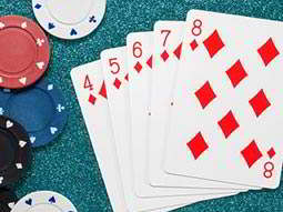 Five red diamond cards laid out next to poker chips
