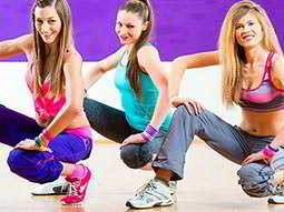 Three girls dancing and crouching down in workout gear