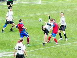 An LNOF player kicks out at a ball surrounded by other players on the pitch at St James Park