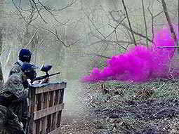 Two people hiding behind a fence and playing paintball with pink smoke in the foreground