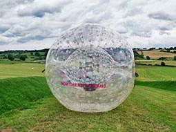 A zorb outdoors, ready to roll down a hill